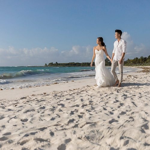 Bride and groom walking towards camera on beach