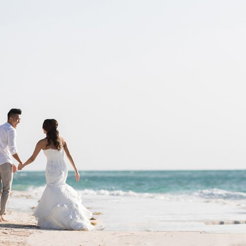 Bride and groom walking by the water on beach in Riveira Maya Mexico