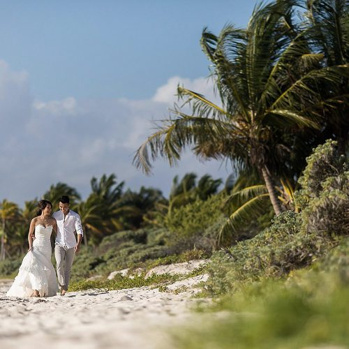 Bride and groom walking on beach with Palm trees in background