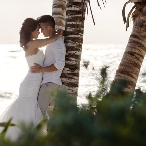 Bride and groom leaning up against a palm tree in romantic pose.
