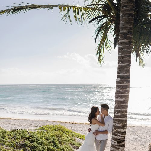 Bride and groom leaning up against a palm tree on beach in Riveira Maya Mexico