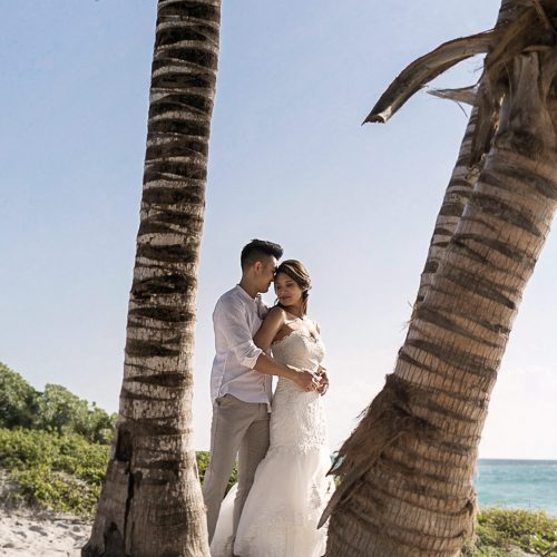 Bride and groom between two palm trees.