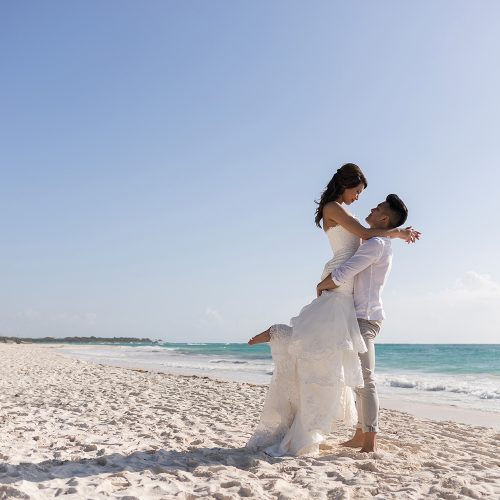 Bride on top of groom on beach in Riveira Maya Mexico