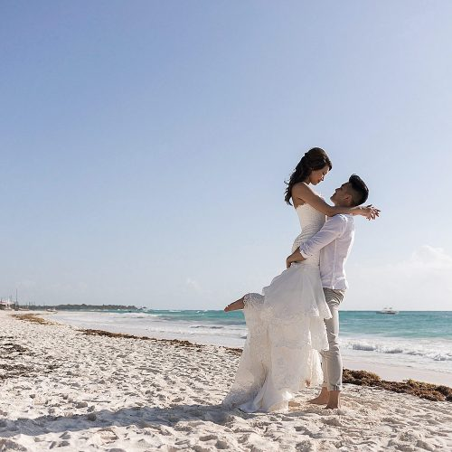 Groom lifting bride on beach in Riviera Maya