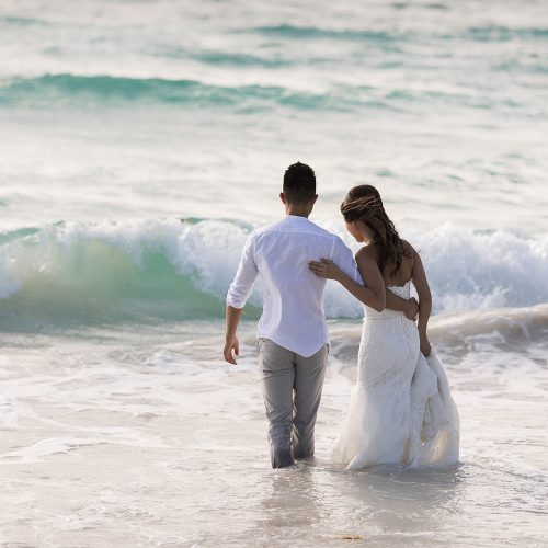 Bride and groom walking into water at TTD on beach in Riveira Maya Mexico