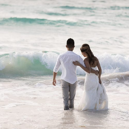 Bride and groom going into water in Riviera Maya