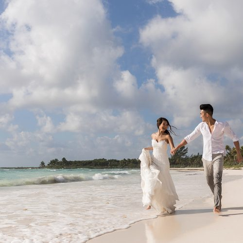 Bride and groom running after walk on beach.