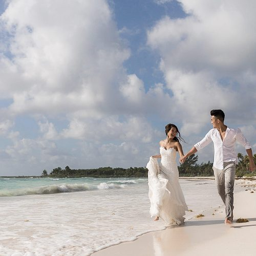 Bride and groom running on beach in Riviera Maya
