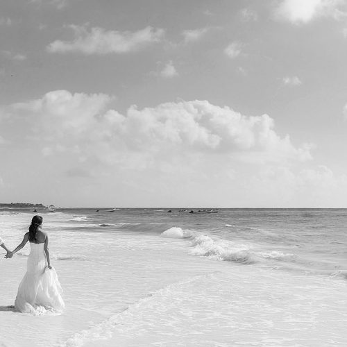 Bride and groom walking away on beach in Riviera Maya