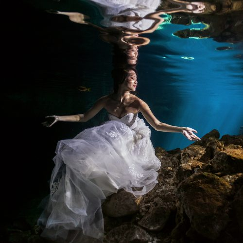 Asian bride underwater in Cenote Trash the Dress (TTD) in Mexico