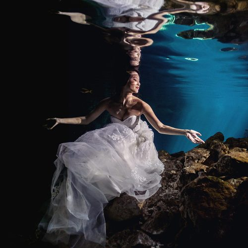 Bride underwater in dress in Cenote