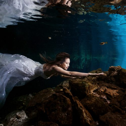 Bride swimming forwards in Cenote Trash the Dress (TTD) in Mexico