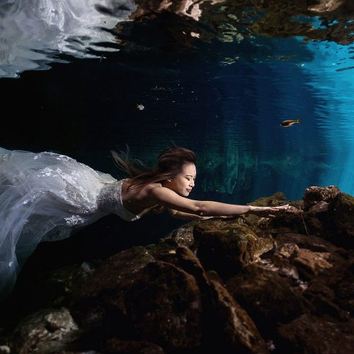 Bride swimming underwater in dress in Riviera Maya