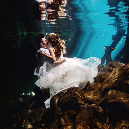 Bride and groom underwater in Trash the dress