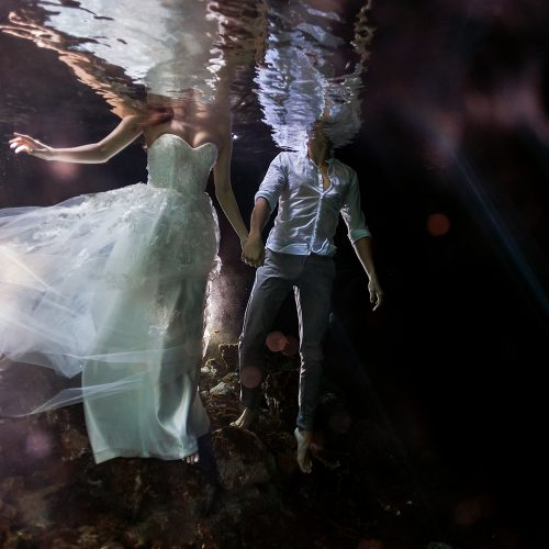 Bride and groom holding hands underwater Cenote Trash the Dress (TTD) in Mexico