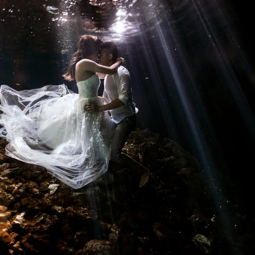 Bride and groom kissing underwater at Cenote Trash the Dress (TTD) in Mexico
