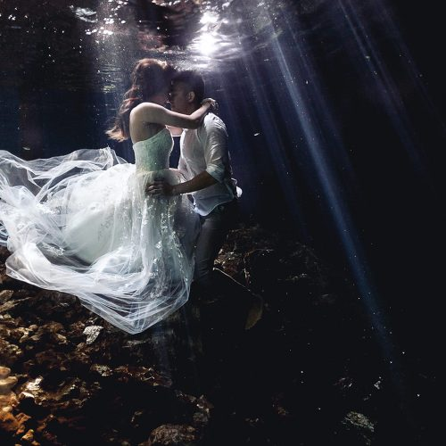 Bride and groom underwater with light rays behind them.