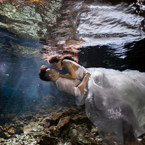 Bride on top of groom in underwater Cenote Trash the Dress (TTD) in Mexico