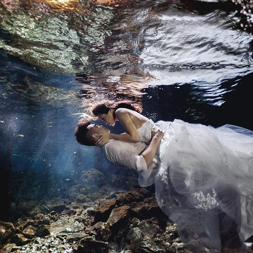 Bride and groom kissing underwater in TTD