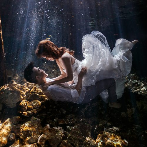 Bride on top of groom in Cenote Trash the Dress (TTD) in Mexico