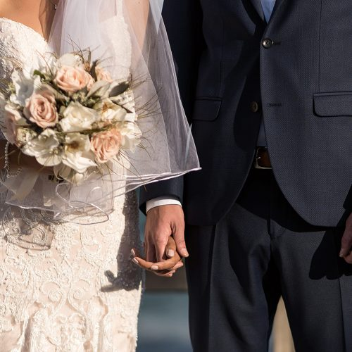 Close up of bride and groom holding hands at wedding