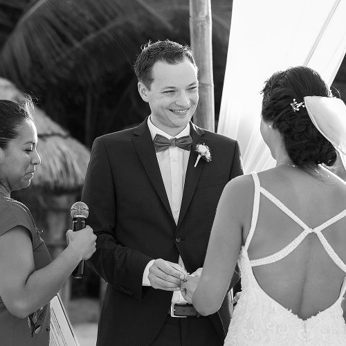 Groom putting on ring at wedding ceremony at Punta Venado, Riviera Maya