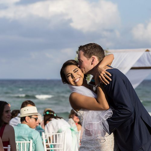 Groom kissing bride laughing at Punta Venado, Riviera Maya Mexico
