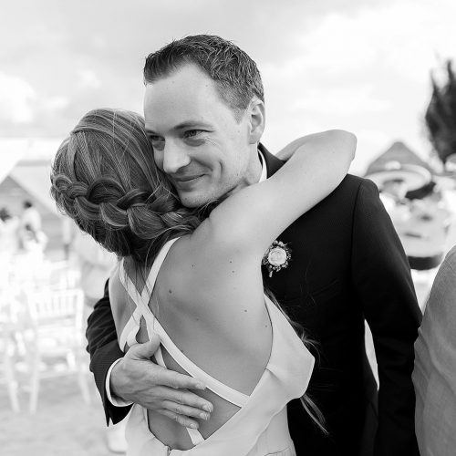 Groom hugging guest after wedding ceremony