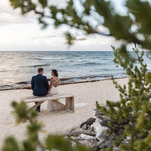 Bride and groom sitting on bench looking at the sea