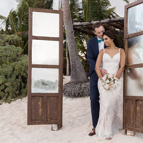 Bride and groom beside old doors at punta venado beach club