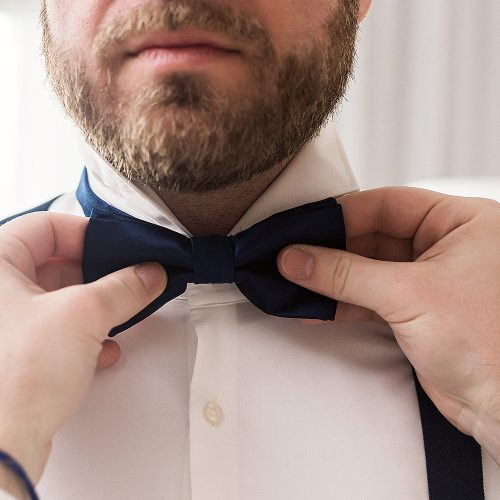 Close up of groom putting on bow tie