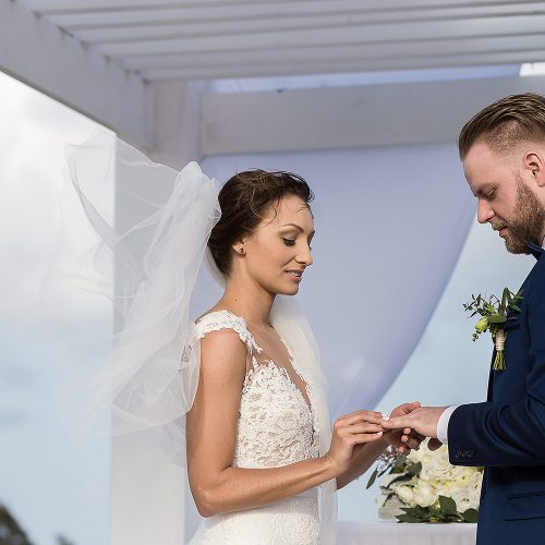 Bride putting on rings during wedding ceremony at Azul Fives sky deck