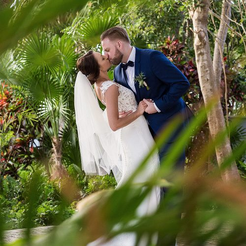Bride and groom kissing in garden at Azul Fives Riviera Maya