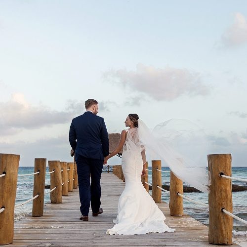 Bride and groom walking on dock at Azul Fives Riviera Maya