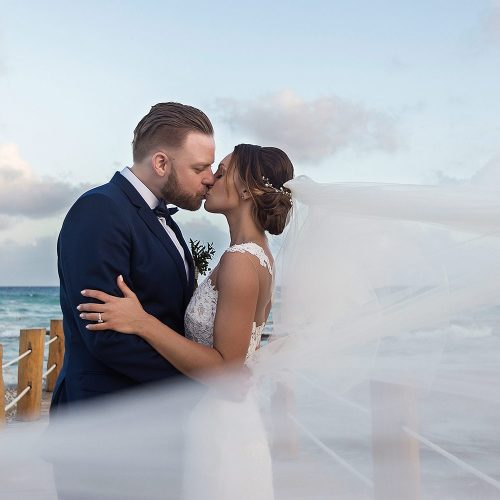 Bride and groom kissing on dock at Azul Fives Riviera Maya
