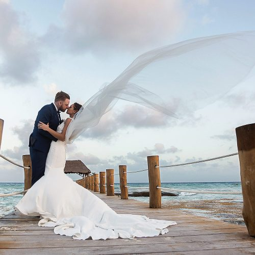 Bride and groom kissing with wind on dock at Azul Fives resort