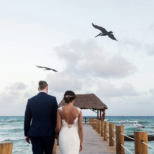 Bride and groom walking on dock with birds in the background in Riviera Maya