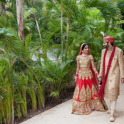 Indian bride and groom walking on holding hands