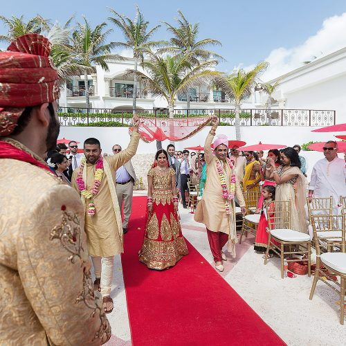 Indian bride waling down aisle towards wedding ceremony in Cancun