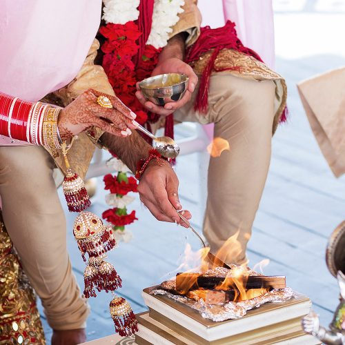Groom putting oil on fire during Indian wedding ceremony.