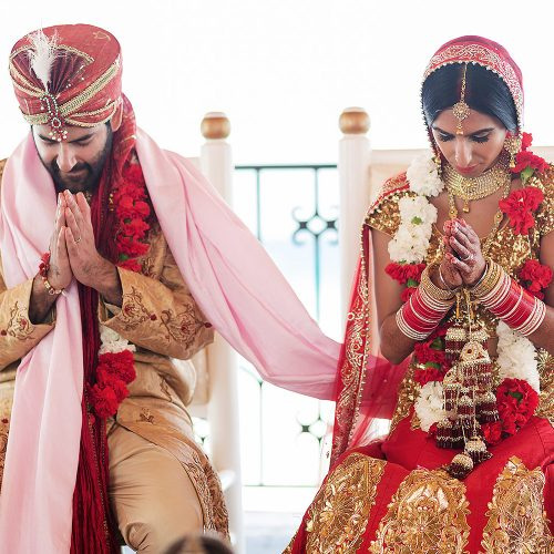 Bride and groom praying during Indian wedding ceremony
