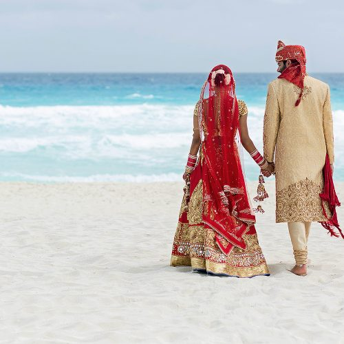 Indian bride and groom on beach after wedding ceremony