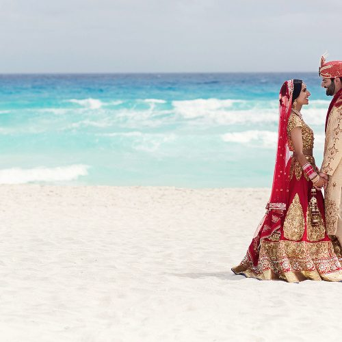 Indian bride and groom on beach in Cancun after wedding.