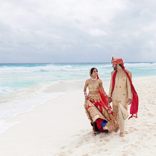 Indian bride and groom walking on beach in Cancun