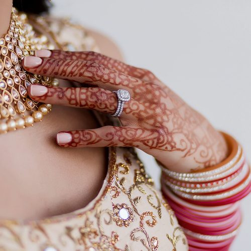 Close up of bride with henna, necklace and wedding ring.