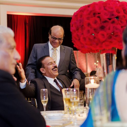 Candid photograph of guests laughing at Indian wedding reception