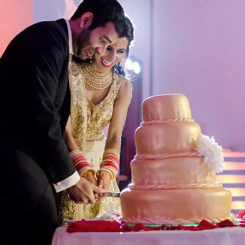 Bride and groom cutting the cake at Indian wedding reception.