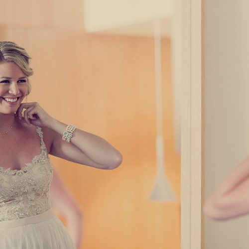 Bride putting on necklace in mirror
