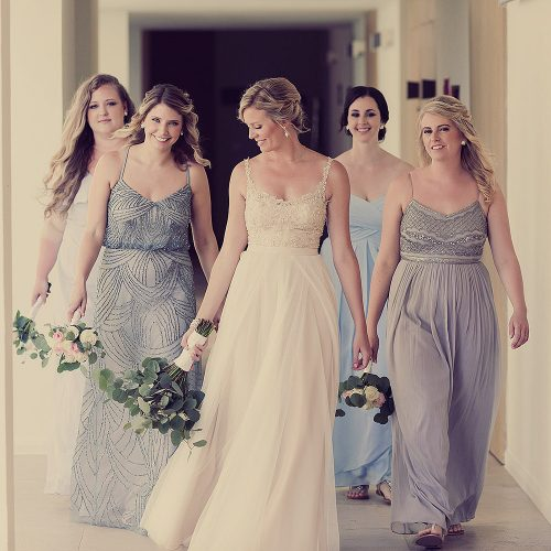 Bride walking with bridesmaids at Finest Playa Mujeres resort.