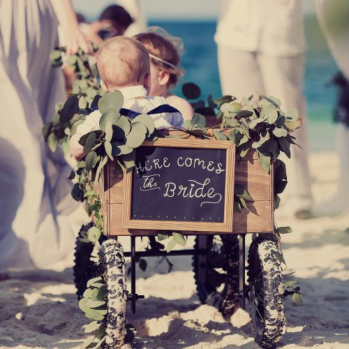 Flower girls in wagon on beach wedding.